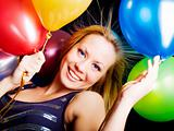 smiling woman holding ballons and celebrating