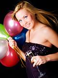 smiling blond woman holding ballons and champagne
