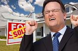 Excited Man in Front of Sold Real Estate Sign and Beautiful New House.