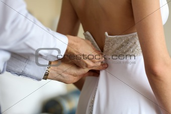 Groom helping birde to put wedding dress on