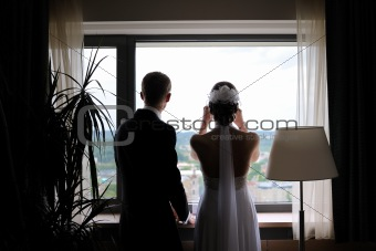 Bride and groom silhouettes against the window