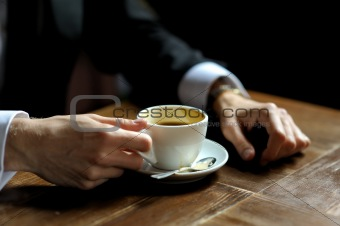 Groom's hands holding cup of coffe