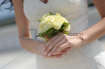 Bride's hands holding wedding bouquet