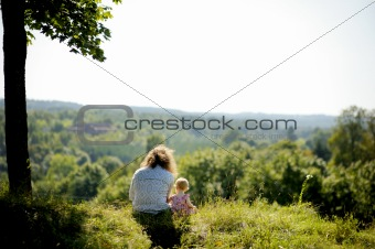 Little baby girl and her father on the edge of a cliff