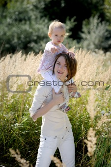 Mother with a baby on her shoulders pointing at you