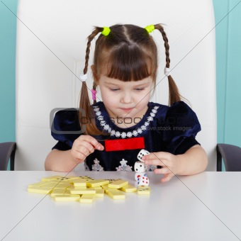 Little girl playing with toys, sitting at table