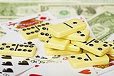 Handful of dominoes on cards and money