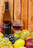 Wine and fruits on background of wooden wall