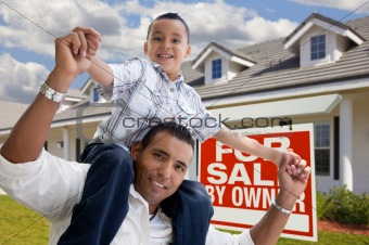 Excited Hispanic Father and Son with For Sale By Owner Sign in Front of House.