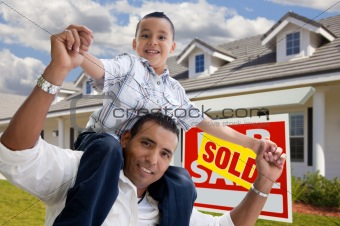Excited Hispanic Father and Son with Sold For Sale Real Estate Sign in Front of House.