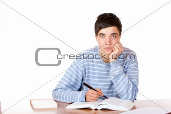 Young handsome male student sitting on desk learning for exam