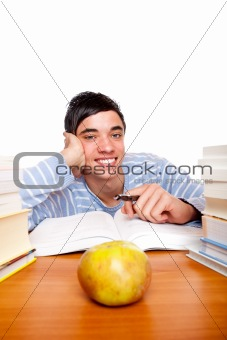Young smiling male student sitting happy between study books
