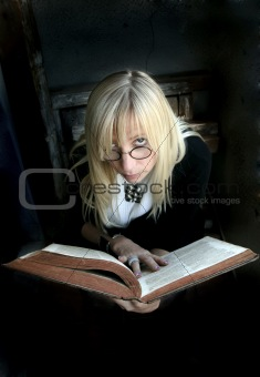 Portrait of the beautiful blonde woman with glasses and old book