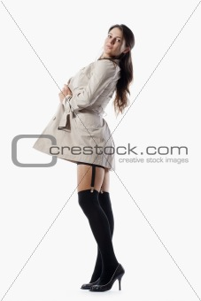 beautiful young woman in trenchcoat and black stockings - isolated on white
