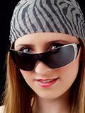 Young blond woman peeking over sunglasses