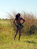 Young black woman in field bare top from back