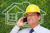 Contractor in Hardhat on His Cell Phone Over House Icon and Blurry Grass.