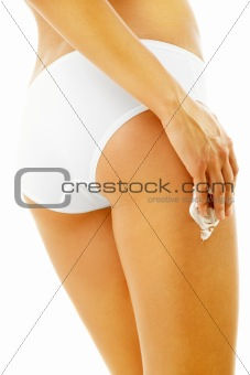 Slim tanned woman applying cosmetics