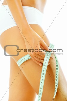 Slim tanned woman measuring her body
