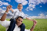 Happy Hispanic Father and Son Over Grass Field, Clouds and Blue Sky.