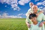Happy African American Family Over Grass Field, Clouds and Blue Sky - Room For Your Own Text to the Left.
