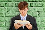 Person reads book on background of green wall