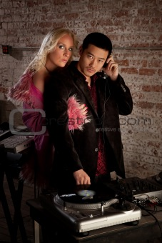 Asian DJ with blond woman at 1970s Disco Music Party