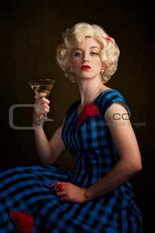 Pretty retro blonde woman in vintage 50s dress with martini