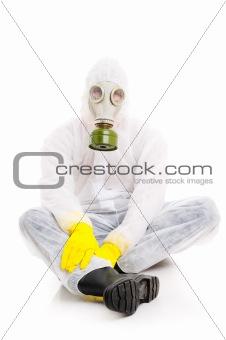 Man in gas mask sitting on floor