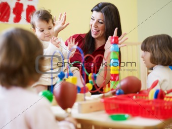 three little girls and female teacher in kindergarten