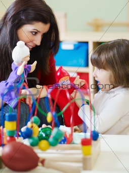 female teacher and little girl playing in kindergarten