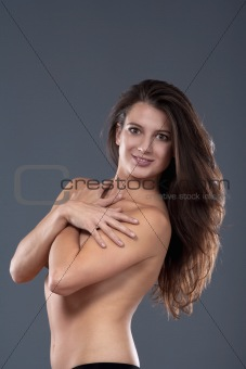 studio portrait of semi-nude brunette with long hair - isolated on gray