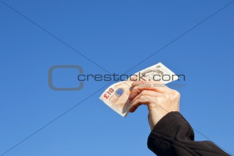 a hand with a ten pound note