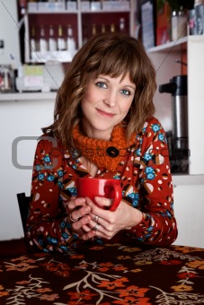 Cute lady with red mug alone in a cafe