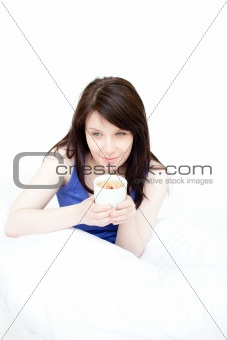 Smiling attractive woman drinking a coffee sitting on her bed