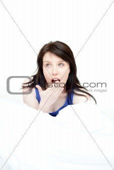 Bright woman yawning sitting on her bed
