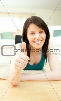 Positive woman with thumbs up lying on the floor
