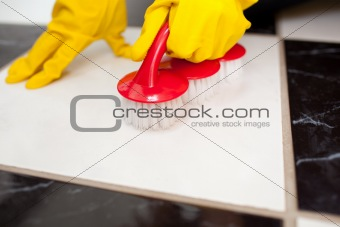 A person cleaning a bathroom's floor with a yellow rubber glove
