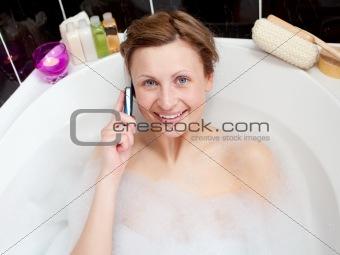 Beautiful woman talking on phone in a bubble bath