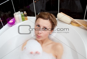 Attractive woman playing in a bubble bath