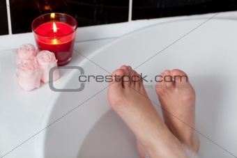 Bathtime. Girl's feet standing in bath tub.