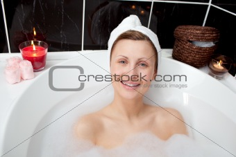 Positive woman relaxing in a bubble bath