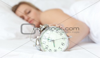 Blond woman holding an alarm clock