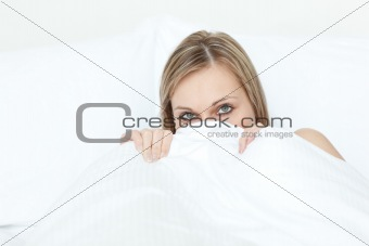 Beautiful woman hiding in her bed