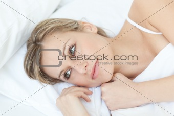 Beautiful relaxed woman lying on her bed