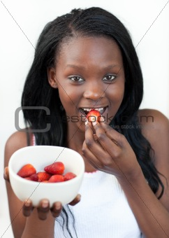 Bright Afro-american a woman eating strawberries