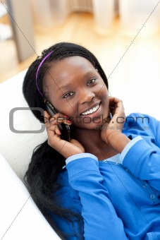 Bright woman listening music with headphones lying on a sofa in the living-room