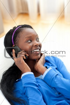 Afro-american woman on phone lying on a sofa