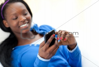 Cute woman sending a text lying on a sofa