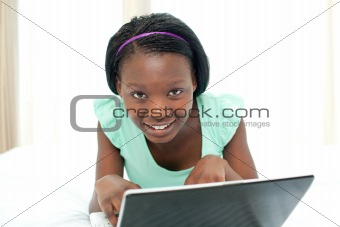 appy teen girl surfing the internet lying on her bed